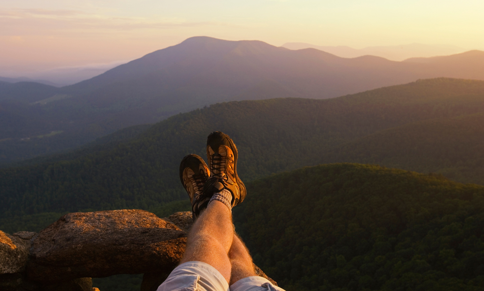 A man relaxing in front of a mountain view.
