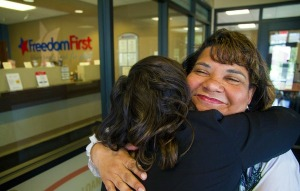 Freedom First's financial educator hugging a member