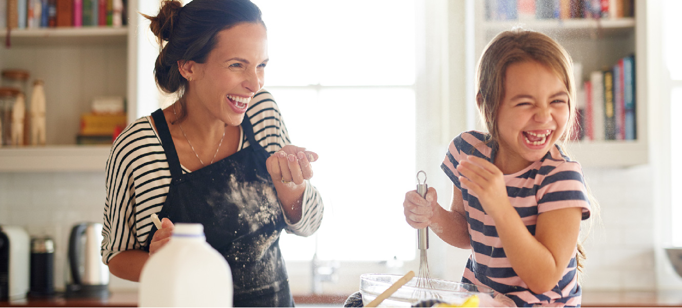 Mother and daughter playfully baking with milk and flour in a modern kitchen.
