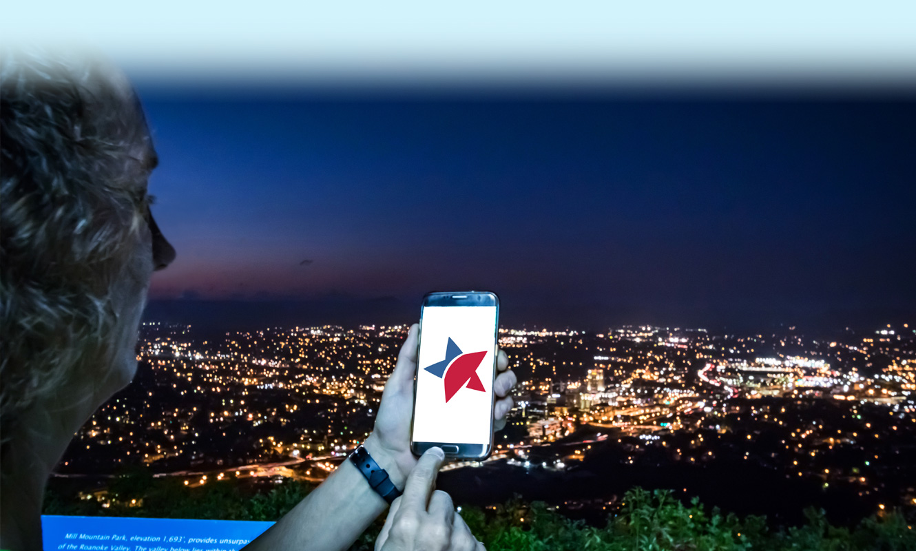 Woman looking at a smartphone screen with the Freedom First logo while standing in front of the Roanoke skyline at night