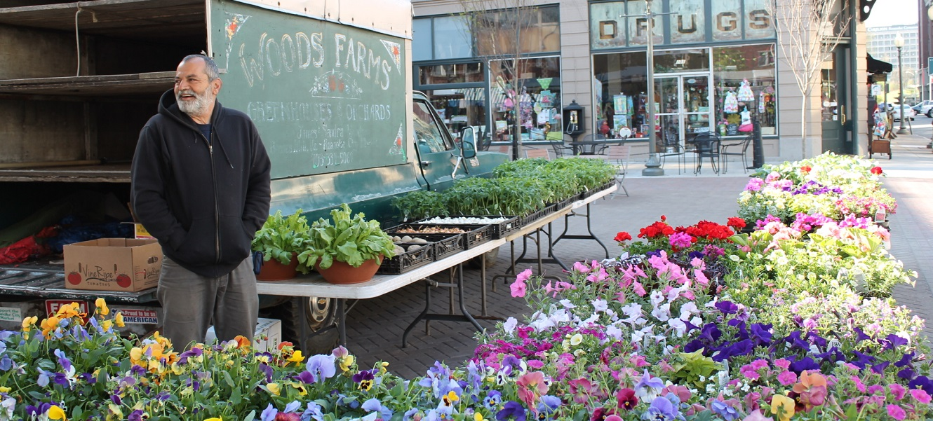 A Roanoke City Market flower vendor stands in front of a truck labeled Woods Farms.