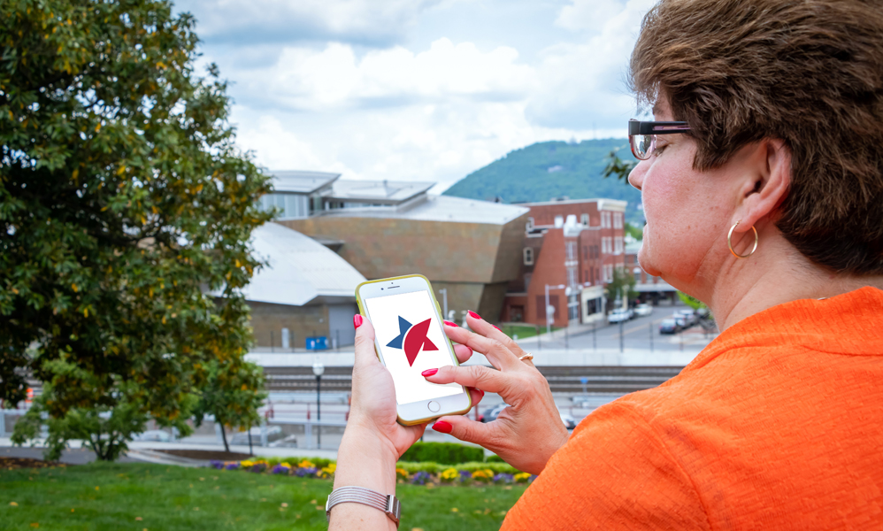 Woman using Freedom First mobile app in downtown Roanoke.