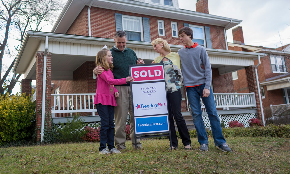 A happy family standing in front of their new home next to a sign that reads: Sold. Financing provided by Freedom First.