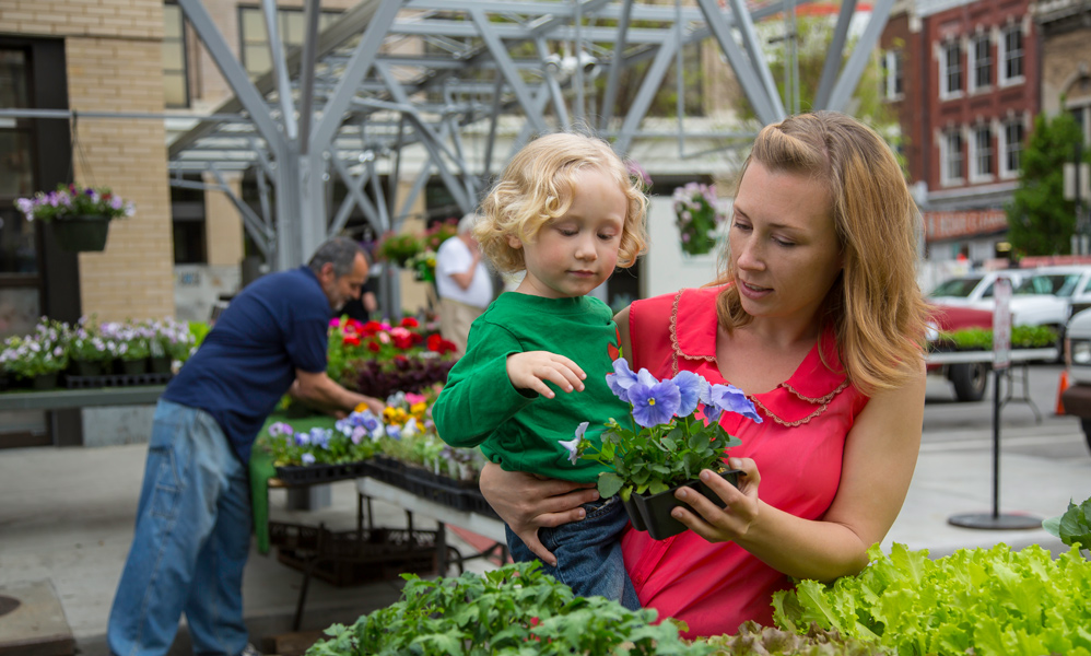 A mother holds a toddler at a flower market and shows him flowers.