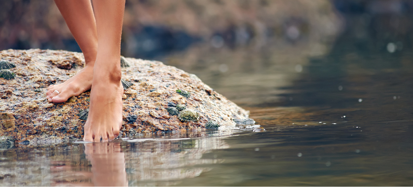 A young woman stands on top of a rock in a shallow river, dipping her toes into the water.