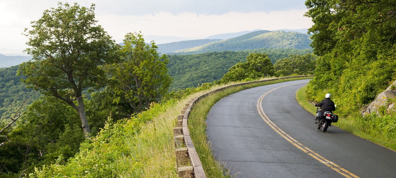 Motorcycle driving on a scenic mountain road.