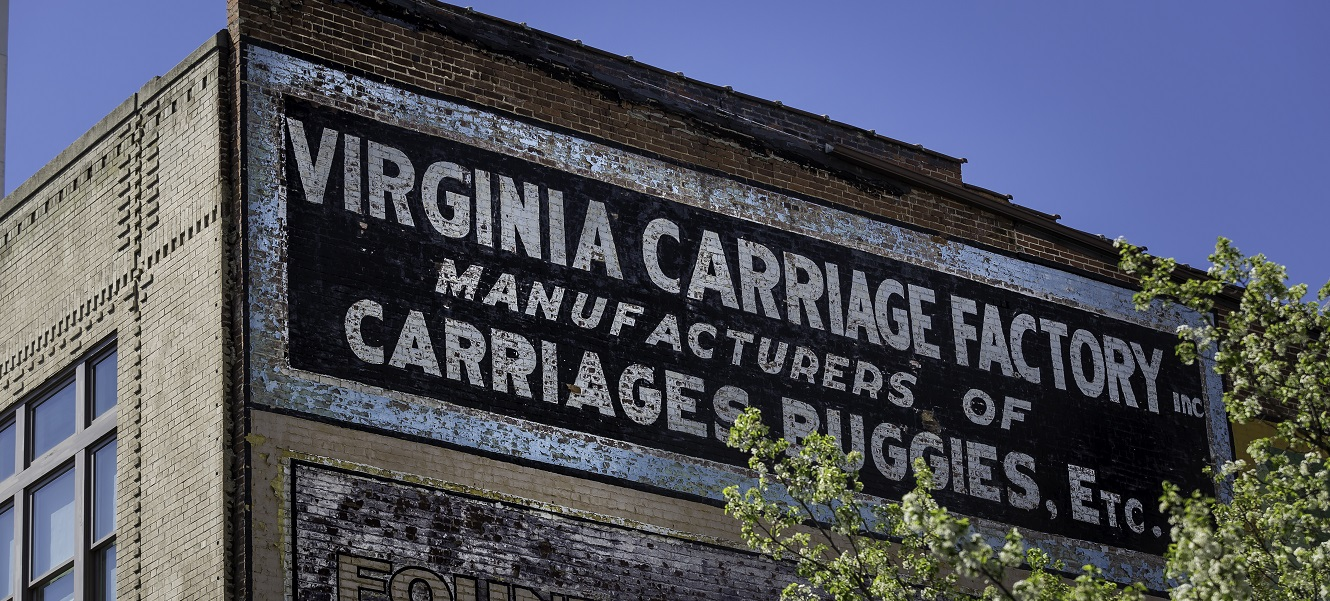 Peeling paint sign on a brick building that reads: Virginia Carriage Factory Inc. Manufacturers of carriages, buggies, etc.