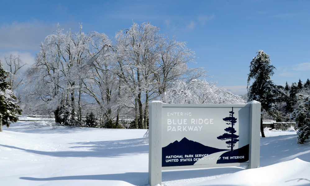 A sign at the entrance of the Blue Ridge Parkway, surrounded by snow.