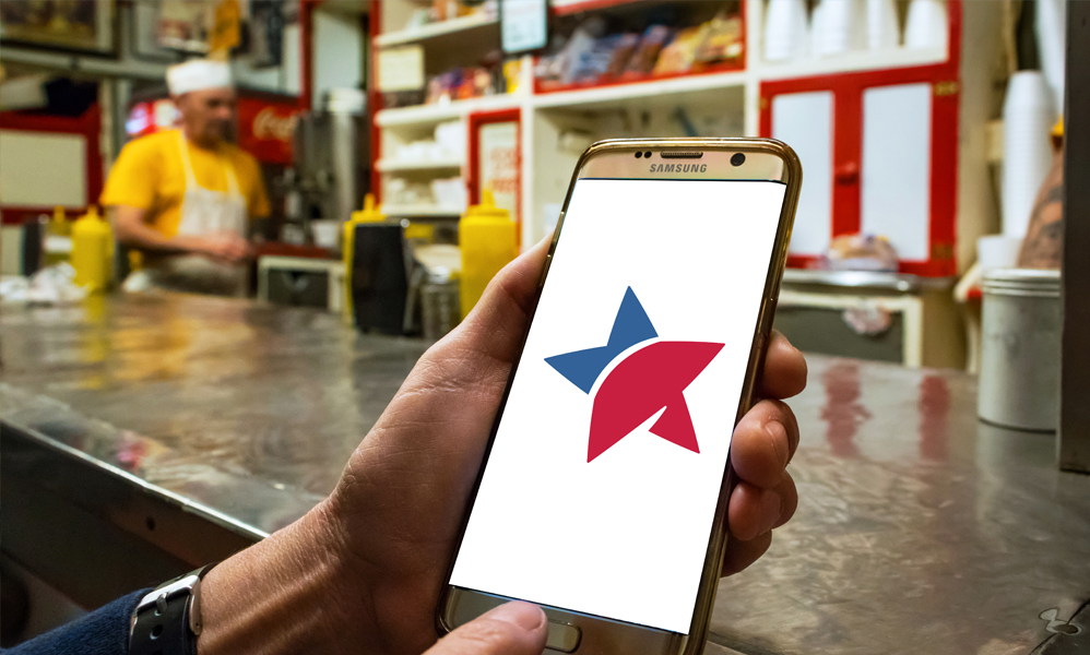 First-person view of someone at the counter at Texas Tavern looking at a smartphone screen with the Freedom First logo