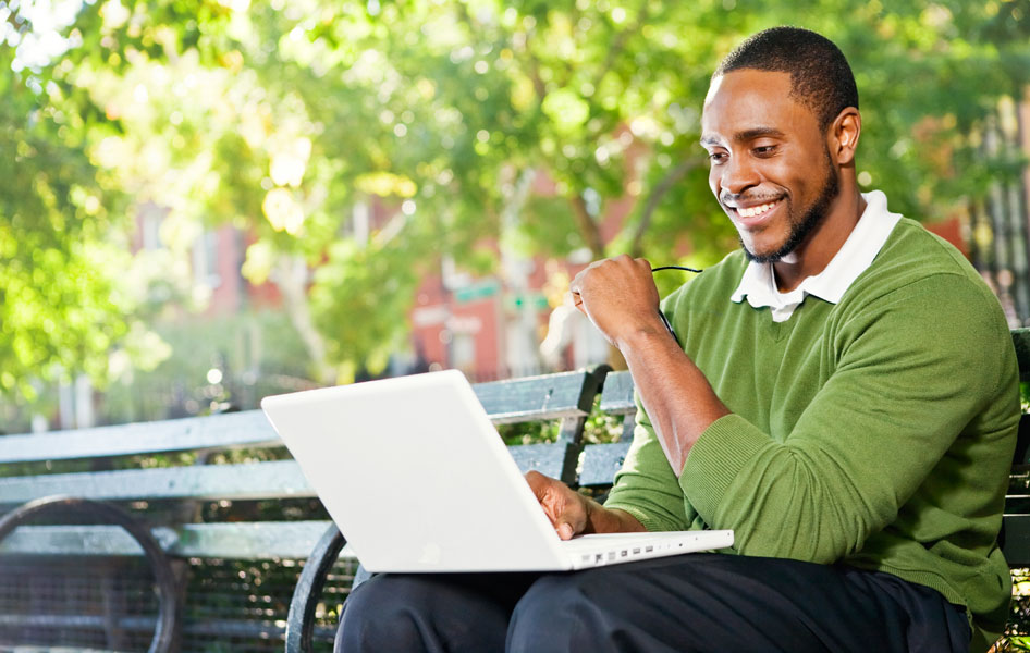 Professional young man on a laptop in a park