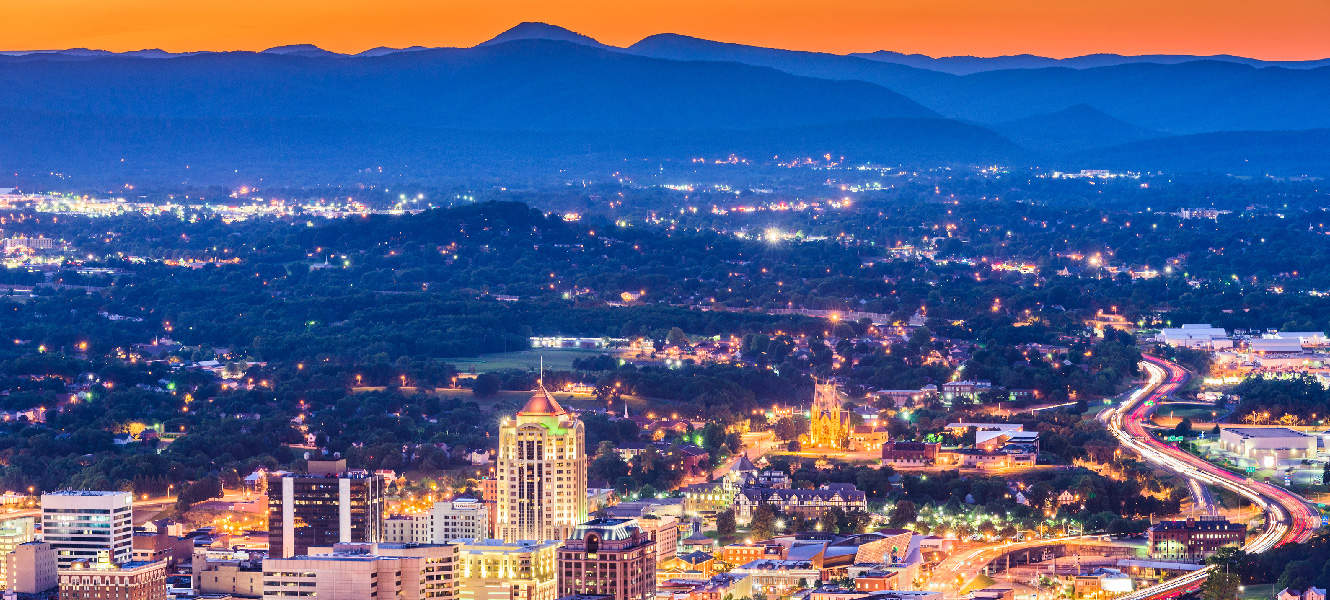 An aerial view of Roanoke city at nighttime with a mountain range in the background.