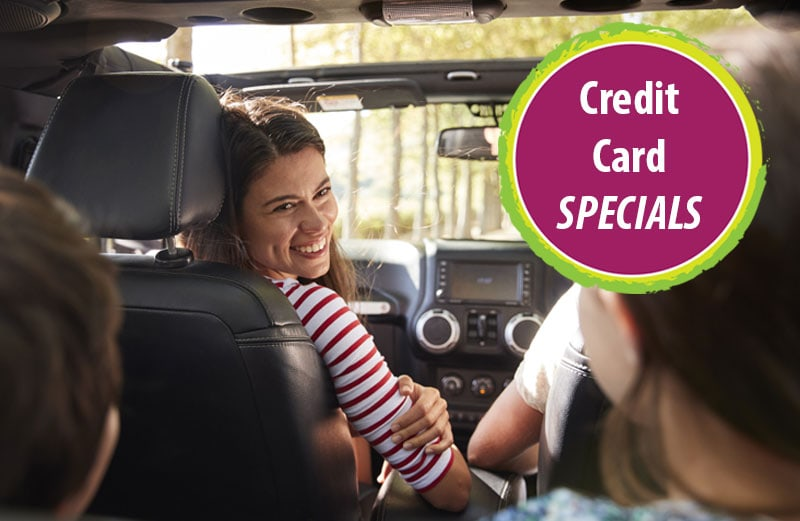 Smiling woman in car with family. Accompanying graphic says credit card specials.