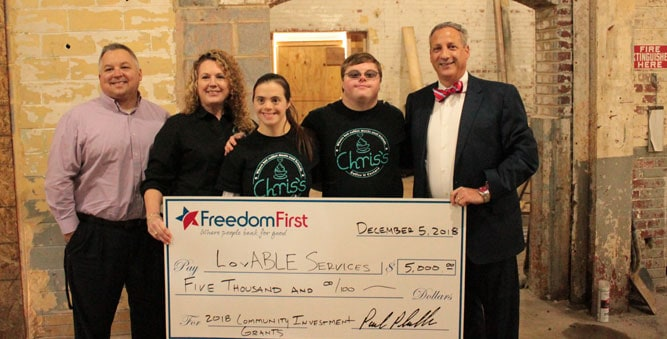 Freedom First employees presenting a $5,000 check to LovABLE Services