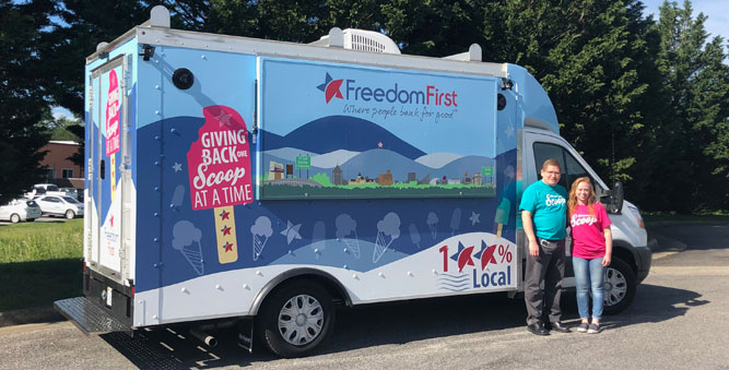 Two Freedom First employees posing in front of the new Scoop ice cream truck.